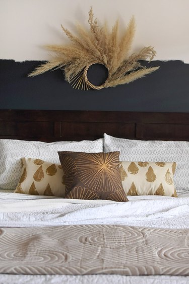 dried pampas grass wreath above bed
