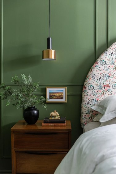 green bedroom with modern pendant light and small painting