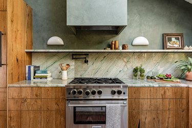 wood kitchen cabinets with green marble countertops and backsplash