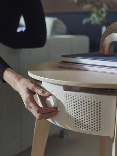 person turning knob on smart air purifier in side table