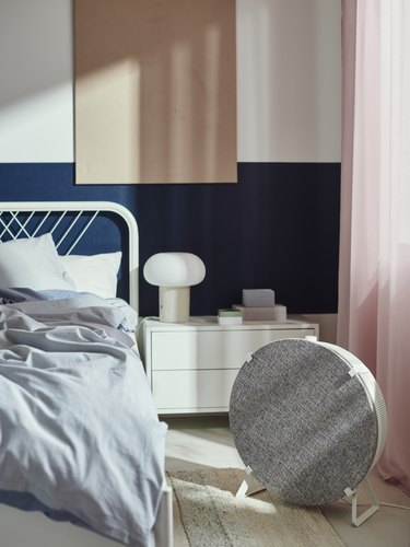 bedroom with gray sheets and pink curtain and gray air purifier on the ground