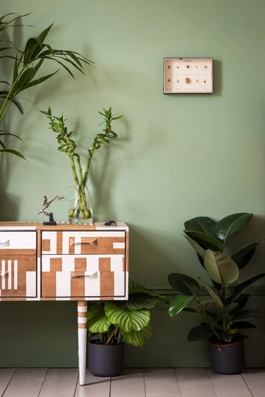 painted wood console in front of green wall with plants
