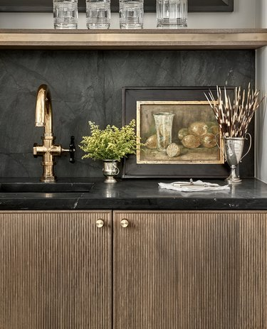wood reeded cabinets with black countertop and backsplash