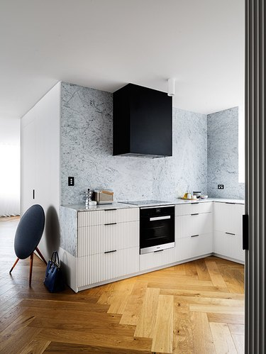 modern kitchen with white reeded cabinets and black hood