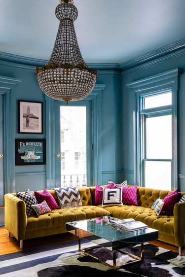 living room with blue walls and yellow sofa