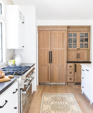 wood reeded cabinets in a white modern farmhouse kitchen