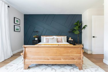 Bedroom with dark teal accent wall and wood bed