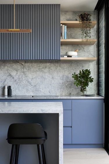 blue reeded cabinets in modern kitchen with marble backsplash