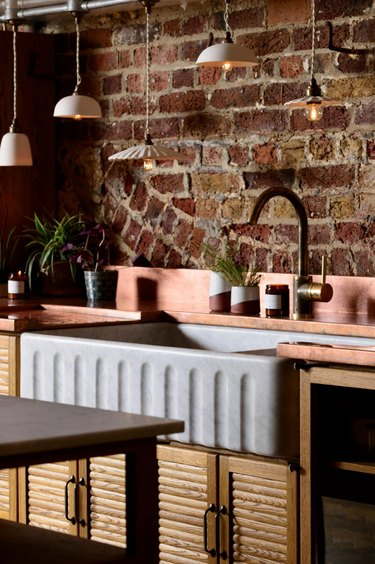 wood reeded cabinets in rustic kitchen with brick wall
