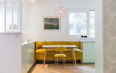 mustard yellow seating with mint green cabinets