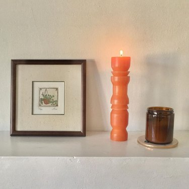 shelf with framed art, and candles