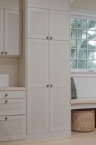 white reeded built-in cabinets with storage basket
