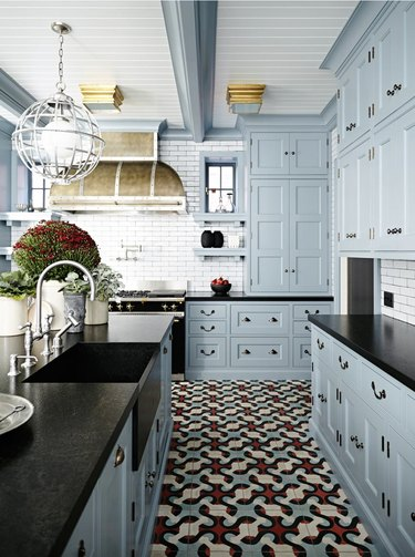 Modern kitchen with blue cabinets, black counter tops and patterned floor tiles.