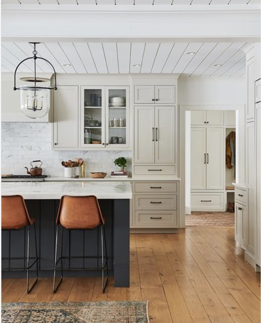 White farmhouse kitchen with countertop cabinets, a grey island and hardwood floors.