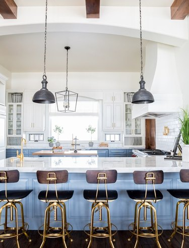 Bright kitchen with light blue island, white cabinets and wood beams on the ceiling.