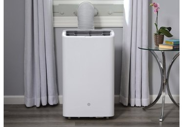 white portable air conditioner; light-gray wall and curtains, white woodwork, and a small glass/metal accent table with books and a pink potted orchid