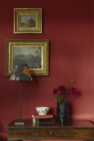 wood console in front of red wall with gold frames