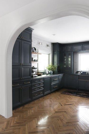 Kitchen with herringbone wood floors, dark cabinets and floating shelves.