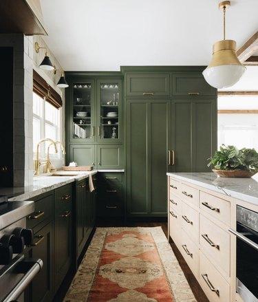 Kitchen with dark green cabinets, beige island and gold hardware.