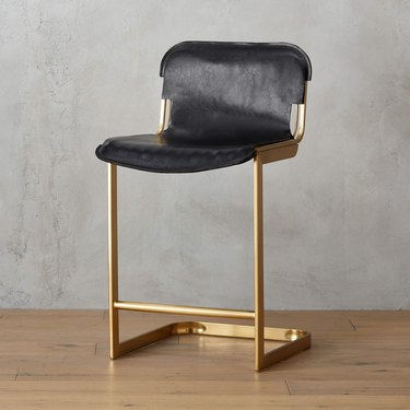 Black leather stool with brass