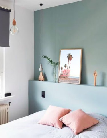 small bedroom with mint green walls and blush colored accents