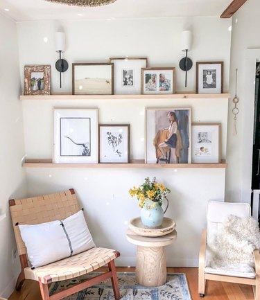 sitting area with two chairs and ledges with framed art