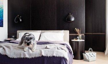 dark bedroom with espresso wood paneling on walls