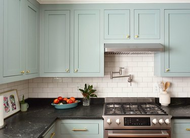 contemporary kitchen with mint green cabinets and white subway tile, black countertops