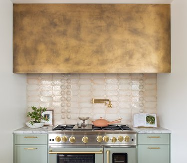 contemporary kitchen with mint green cabinets, large stove with a pink tiled backsplash