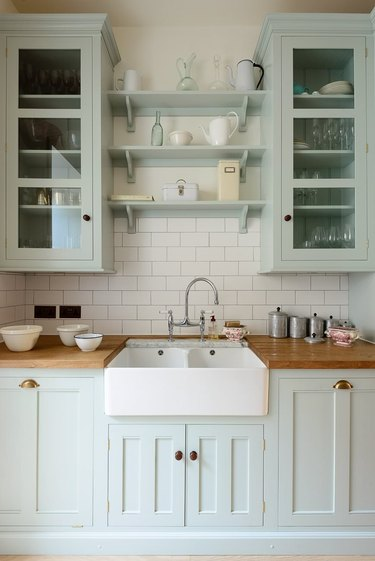 farmhouse kitchen with butcher block counters and a farmhouse sink, mint green cabinets
