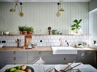 mint green beadboard wall paneling above tile backsplash and wood shelf