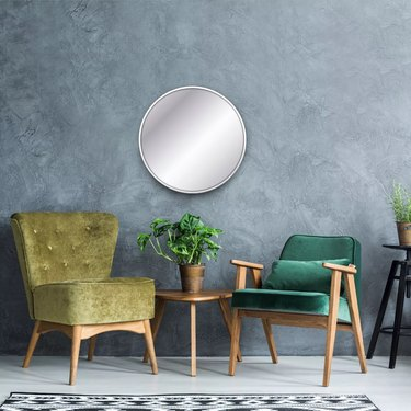 Circular mirror with accent chairs