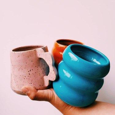 hand holding three colorful mugs