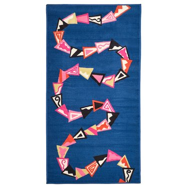blue rug with winding collage-like pattern in various colors