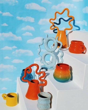 photo with cloud background and white steps with colorful ceramic mugs