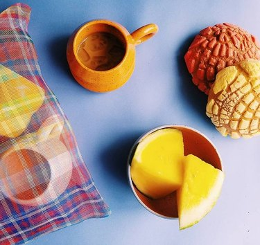 overhead shot of table with bag and ceramics and fruit and two pan dulce breads