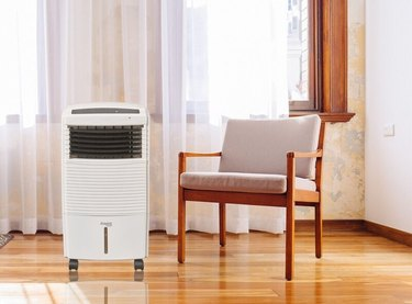 White portable air conditioner in a bright corner of a room with white sheer curtains, a beige upholstered and wood chair, and polished floors