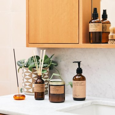 bathroom sink with hand soap bottle and other fragrance products