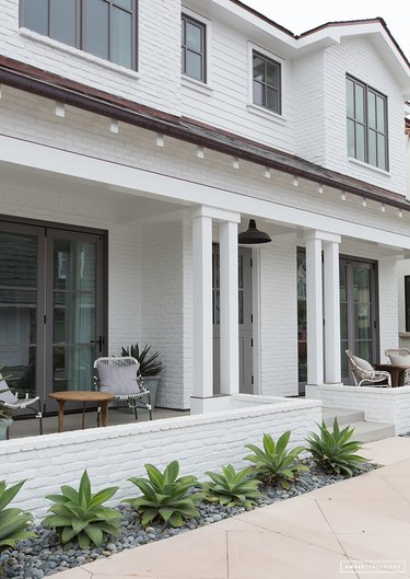 white porch surrounded by succulents
