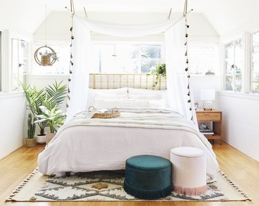 Bedroom with canopy, poufs, rug, plants