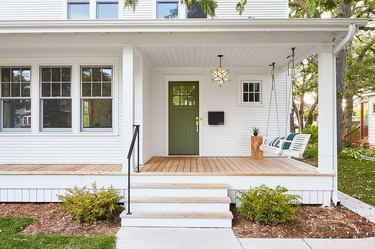 white home with green front door and minimal decor.