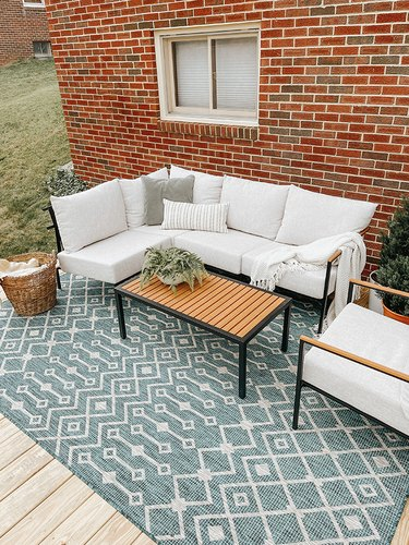 Finish your new DIY deck off with outdoor furniture and a rug.