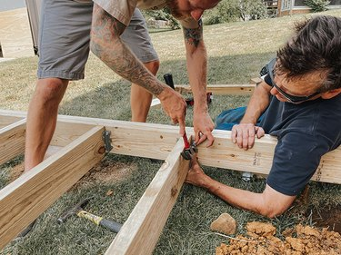 Use joist hangers to attach joists to the deck frame.