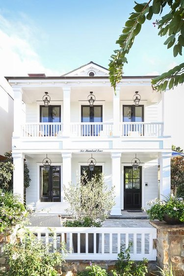 white double porch with black trim and series of windows