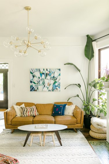 Living room with sputnik chandelier and camel leather couch.
