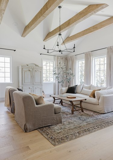 Rustic living room with beamed ceiling and dainty black chandelier.