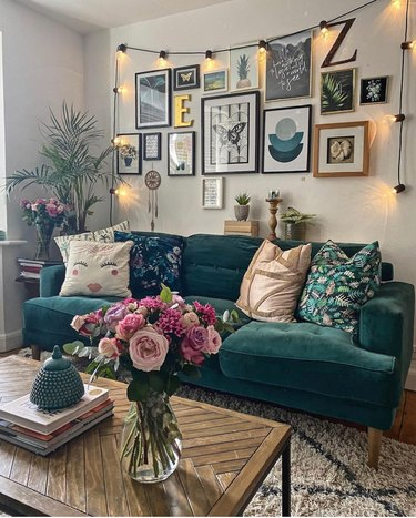 Eclectic living room with green sofa, gallery wall and string lights.