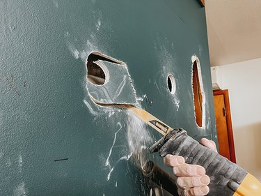 Cut exploratory holes through the drywall using a reciprocating saw.