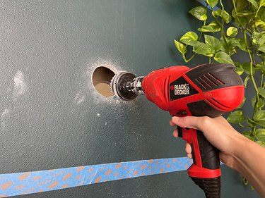 Cut exploratory holes through the drywall using a hole saw attached to a drill.