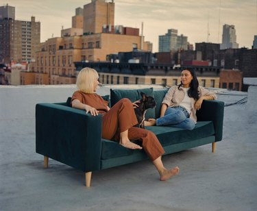 two people sitting on green couch with city landscape in the background